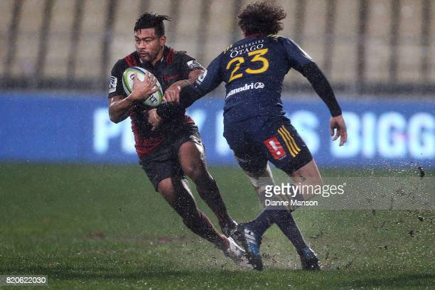 Richie Mo'unga of the Crusaders slips through the tackle of Marty Banks of the Highlanders during the Super Rugby Quarter Final match between the...