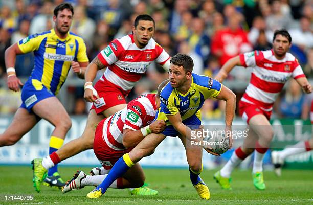 Richie Myler of Warrington looks to pass in the tackle of Wigan's Lee Mossop during the Super League match between Warrington Wolves and Wigan...