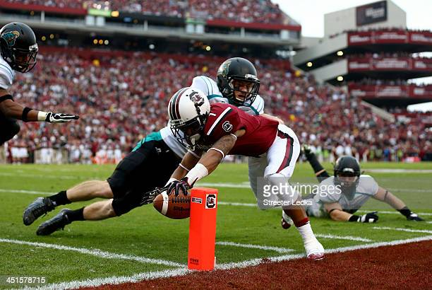 Richie Sampson of the Coastal Carolina Chanticleers tries to stop Damiere Byrd of the South Carolina Gamecocks from diving for a touchdown during...