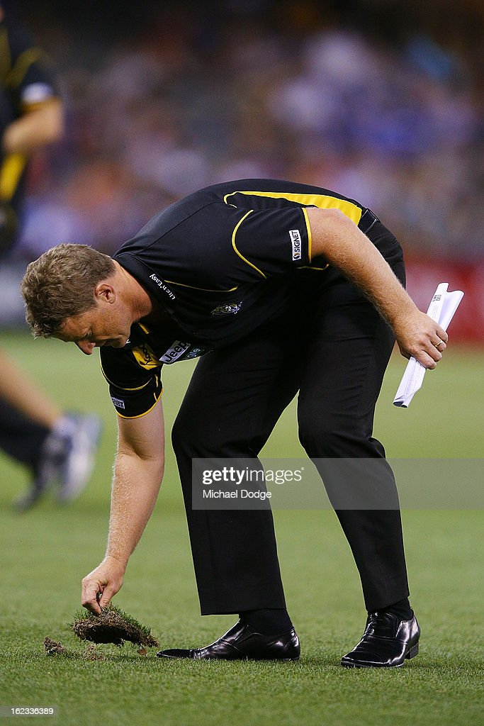 Richmond Tigers coach <a gi-track='captionPersonalityLinkClicked' href=/galleries/search?phrase=Damien+Hardwick&family=editorial&specificpeople=162730 ng-click='$event.stopPropagation()'>Damien Hardwick</a> replaces the turf during the round one AFL NAB Cup match between the Richmond Tigers and the Melbourne Demons at Etihad Stadium on February 22, 2013 in Melbourne, Australia.