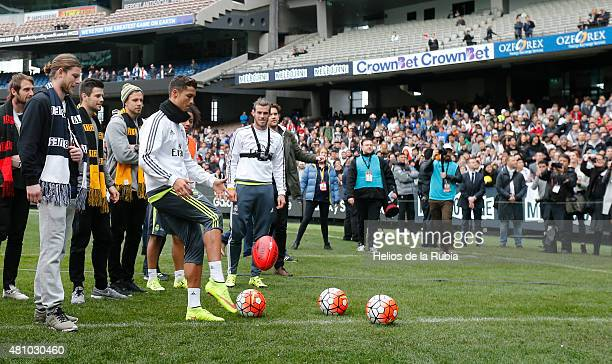 Richmond Tigers player Trent Cotchin shows Cristiano Ronaldo of Real Madrid how to kick an Australian Rules football during a Real Madrid training...