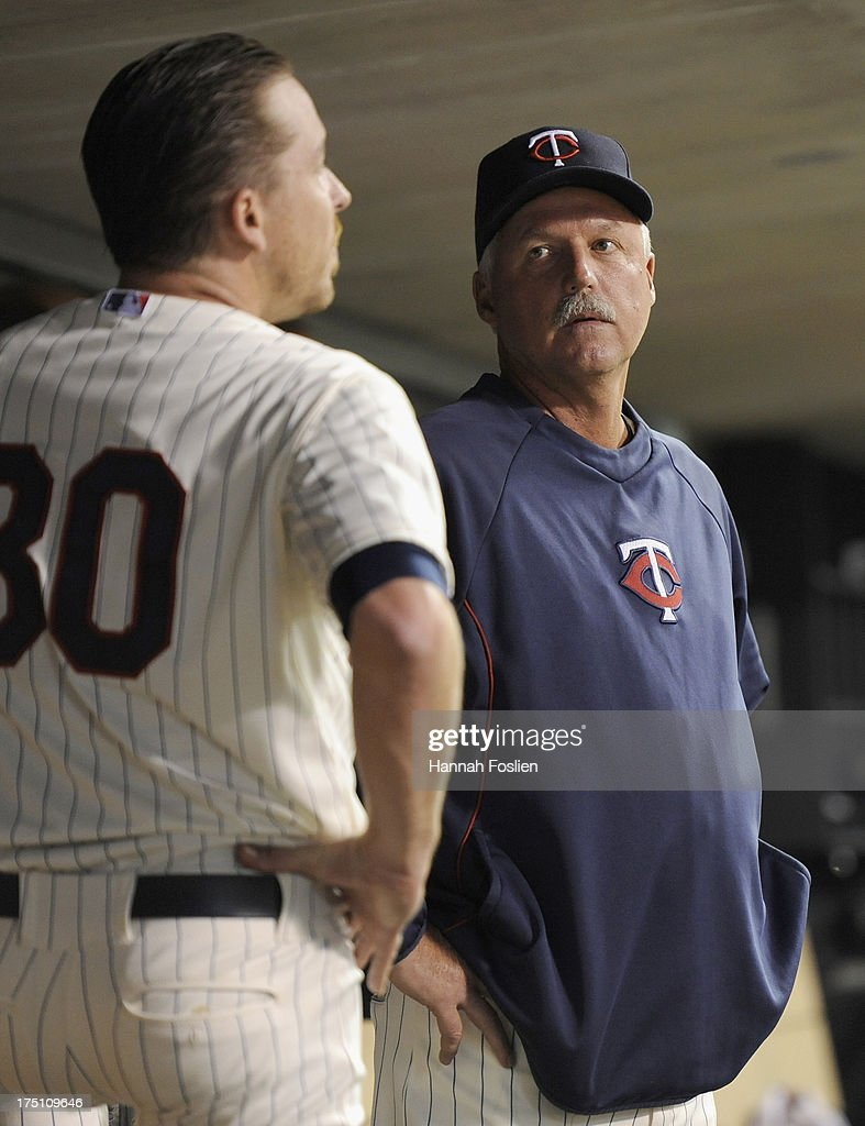 Rick Anderson #40 of the Minnesota Twins speaks with Kevin Correia #30 in the dugout during the sixth inning of the game on July 31, 2013 at Target Field in Minneapolis, Minnesota. The Royals defeated the Twins 4-3.