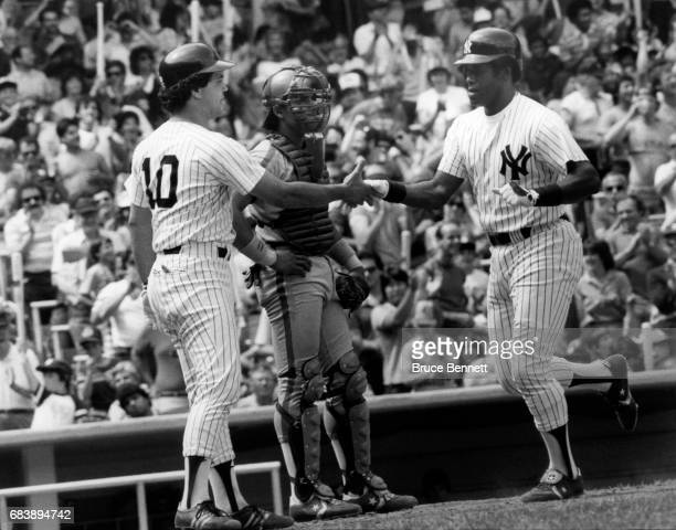 Rick Cerone of the New York Yankees congratulates teammate Ken Griffey Sr #33 after Griffey hit a home run during an MLB game against the Seattle...