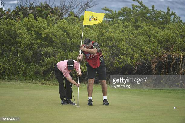 Rick Cochren III and a caddy try to remove a pin on the 13th green during the first round of The Bahamas Great Exuma Classic at Sandals Emerald Reef...