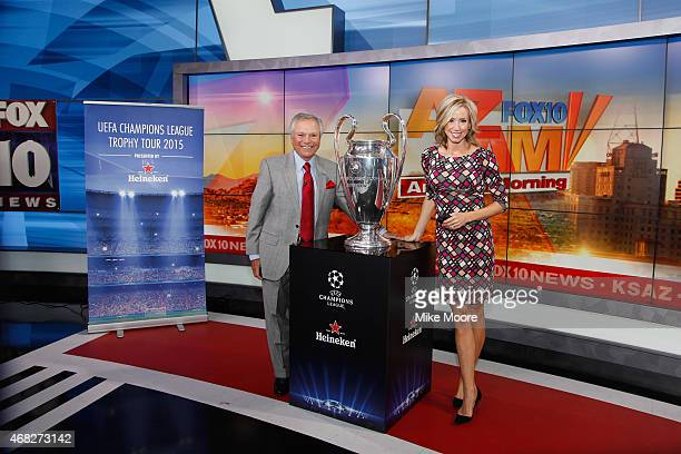 Rick D'Amico and Andrea Robinson from Fox 10 news pose with the UEFA Champions League Trophy Tour presented by Heineken at Fox 10 Studios on March 31...