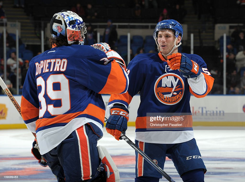 Rick DiPietro #39 of Team Blue is congratulated by Casey Cizikas #53 after defeating Team White during a scrimmage match between players of the New York Islanders and Bridgeport Sound Tigers on January 16, 2013 at Nassau Veterans Memorial Coliseum in Uniondale, New York.