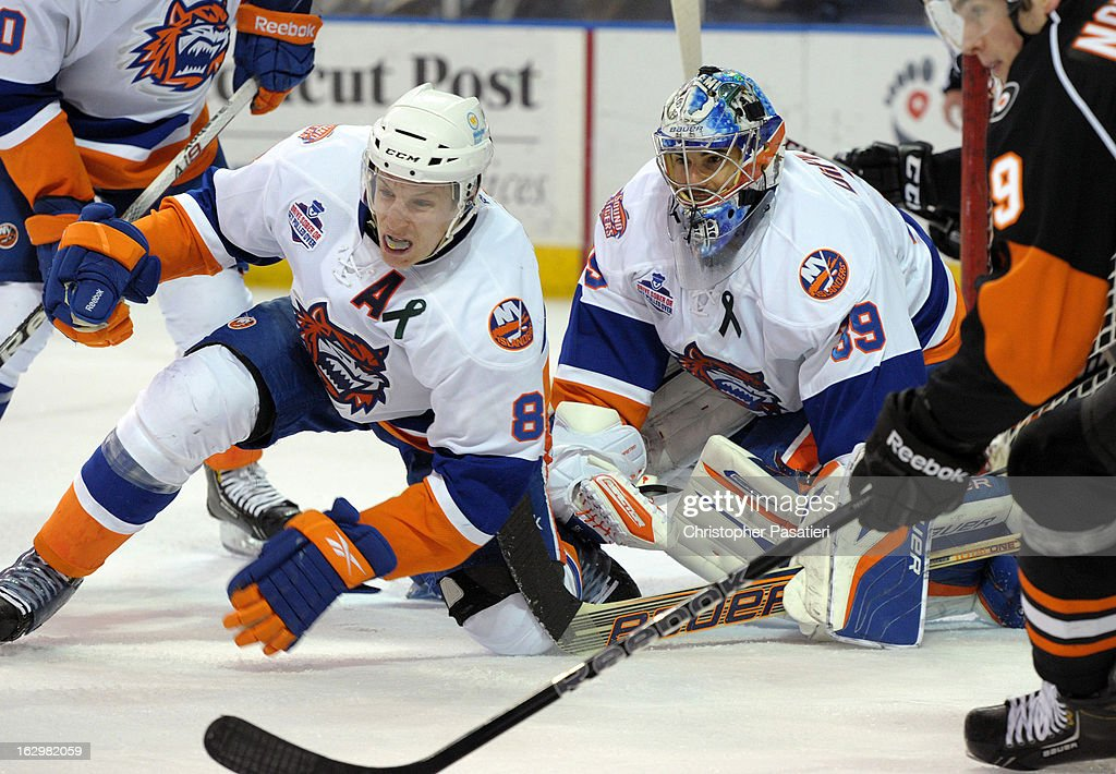 Rick DiPietro #39 of the Bridgeport Sound Tigers and Nathan McIver #8 look on after McIver cleared a puck from the front of the net during an American Hockey League game against the Adirondack Phantoms on March 2, 2013 at the Webster Bank Arena at Harbor Yard in Bridgeport, Connecticut.