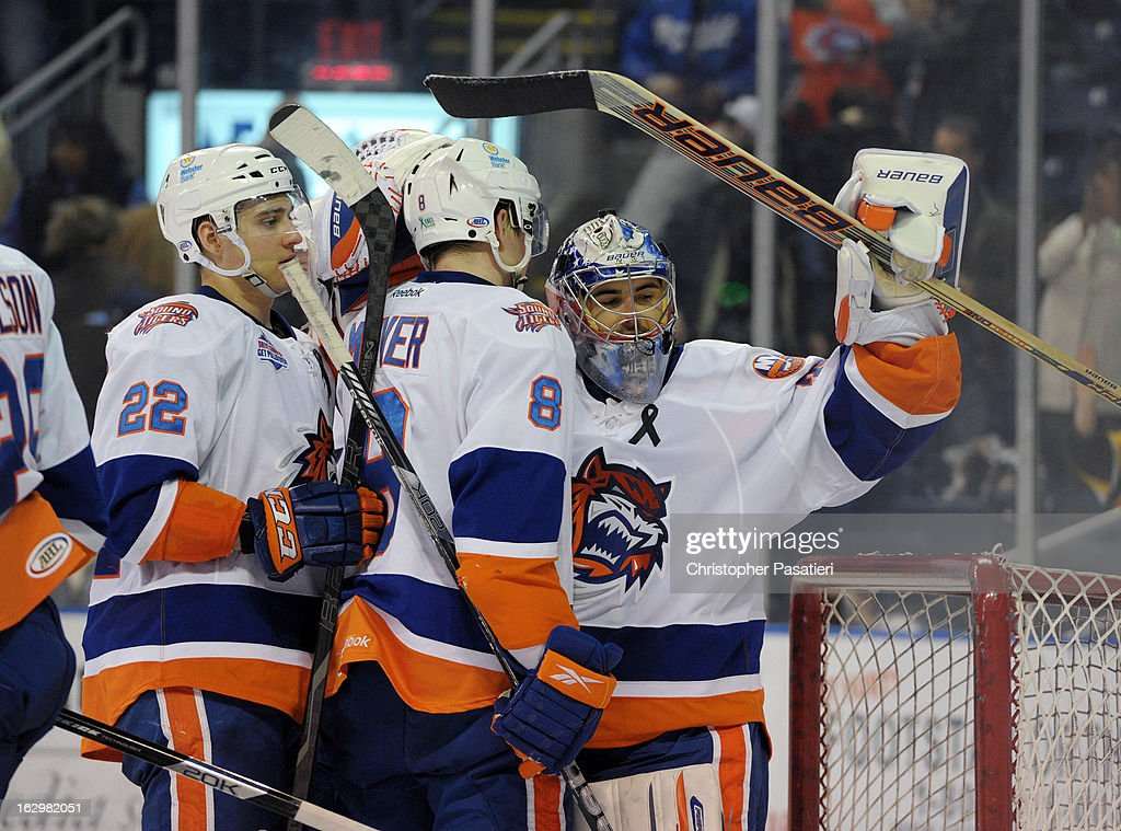 Rick DiPietro #39 of the Bridgeport Sound Tigers is congratulated by Nino Niederreiter #22 and Nathan McIver #8 after defeating the Adirondack Phantoms during an American Hockey League on March 2, 2013 at the Webster Bank Arena at Harbor Yard in Bridgeport, Connecticut.