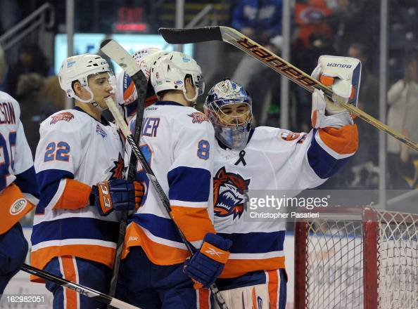 Rick DiPietro of the Bridgeport Sound Tigers is congratulated by Nino Niederreiter and Nathan McIver after defeating the Adirondack Phantoms during...