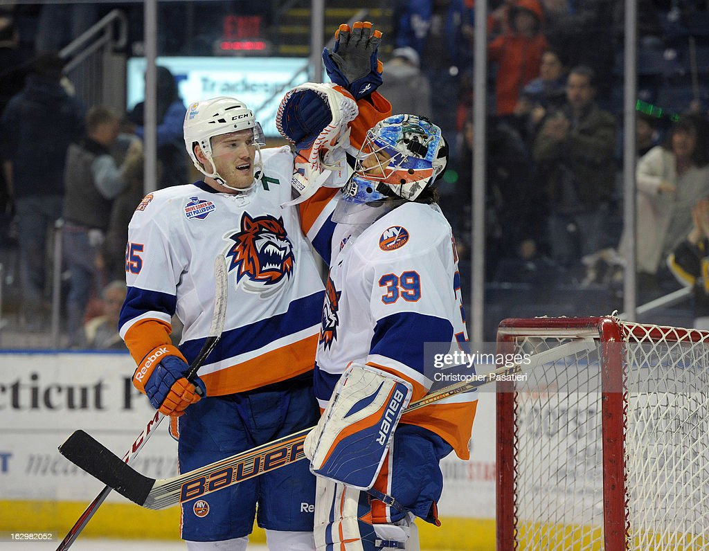 Rick DiPietro #39 of the Bridgeport Sound Tigers is congratulated by Jordan Hill #25 after defeating the Adirondack Phantoms during an American Hockey League on March 2, 2013 at the Webster Bank Arena at Harbor Yard in Bridgeport, Connecticut.