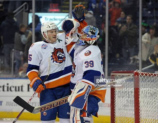 Rick DiPietro of the Bridgeport Sound Tigers is congratulated by Jordan Hill after defeating the Adirondack Phantoms during an American Hockey League...