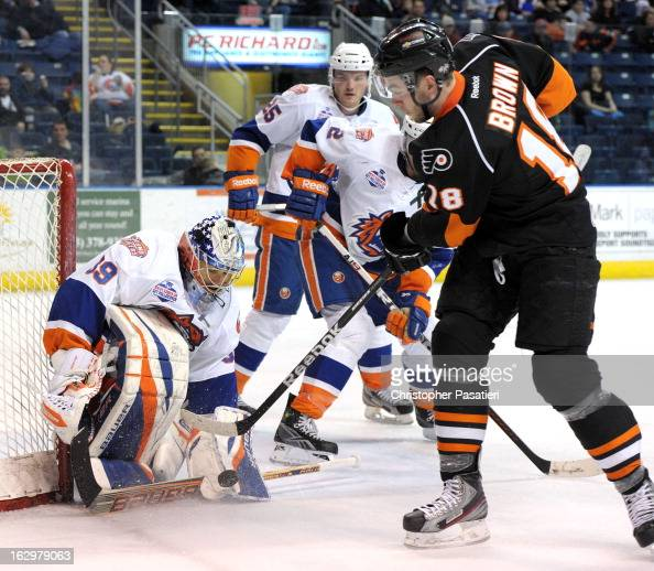 Rick DiPietro of the Bridgeport Sound Tigers makes a save against Tyler Brown of the Adirondack Phantoms an American Hockey League game on March 2...