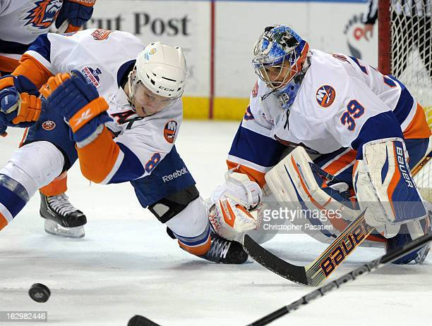 Rick DiPietro of the Bridgeport Sound Tigers watches as Nathan McIver clears the puck from the front of the net during an American Hockey League game...