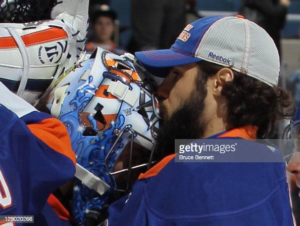 Rick DiPietro of the New York Islanders kisses the mask of goaltender Al Montoya following a 21 victory over the Minnesota Wild at Nassau Veterans...