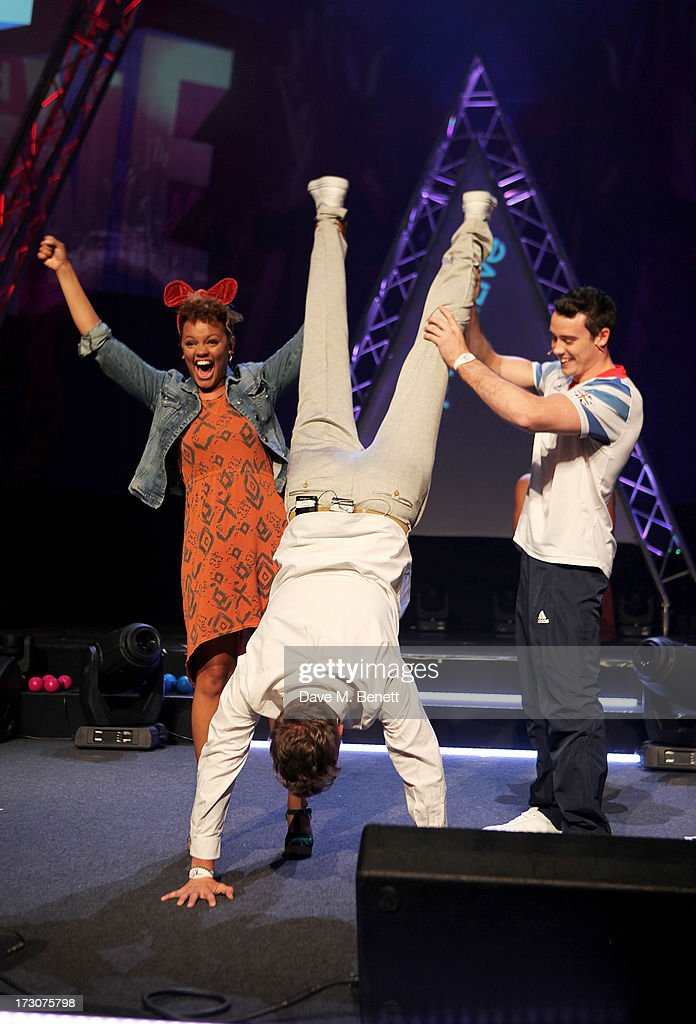 Rick Edwards (C) does a handstand held up by Gemma Cairney and olympian Kristian Thomas on stage at vInspired Live, a youth social change event, at The Roundhouse on July 6, 2013 in London, England.