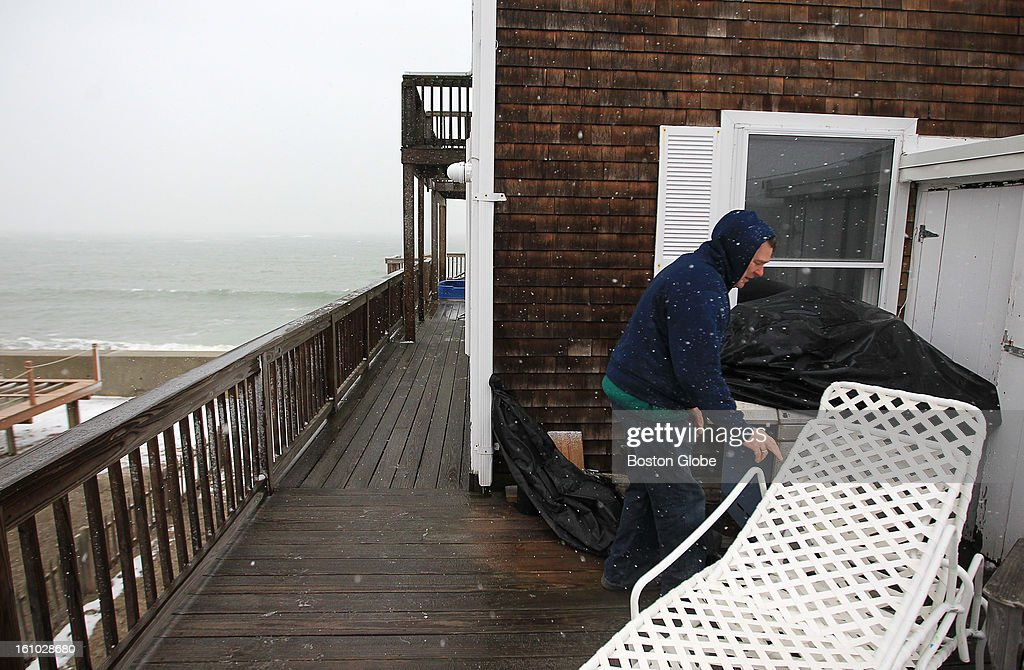 Rick Harrington shuffles some deck furniture at his Scituate home in preparation for the blizzard.