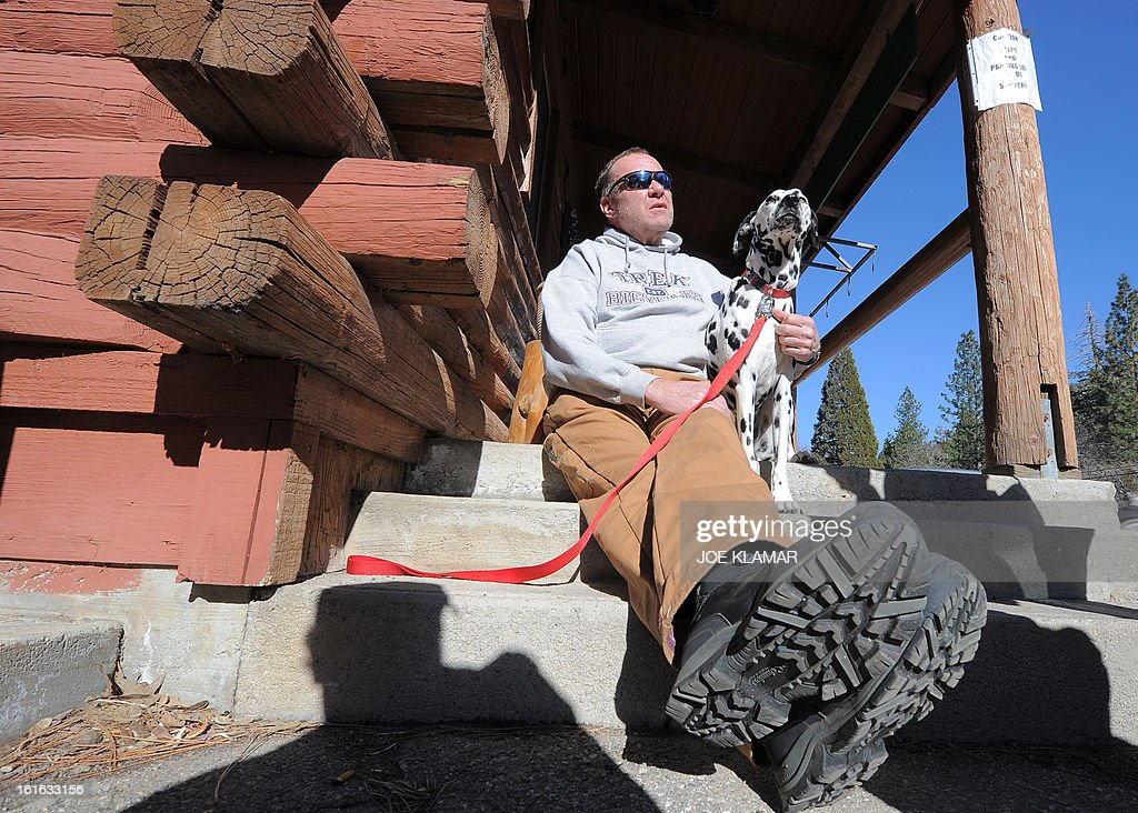 Rick Heltebrake, who called police informing them that fugitive Christopher Dorner had hijacked his car, talks to the media with his dog Suni about the ordeal in Angelus Oaks, California, February 13, 2013. Suspected cop killer Dorner is believed to have been killed in a shoot-out at a cabin in the San Bernardino Mountains. AFP PHOTO / JOE KLAMAR