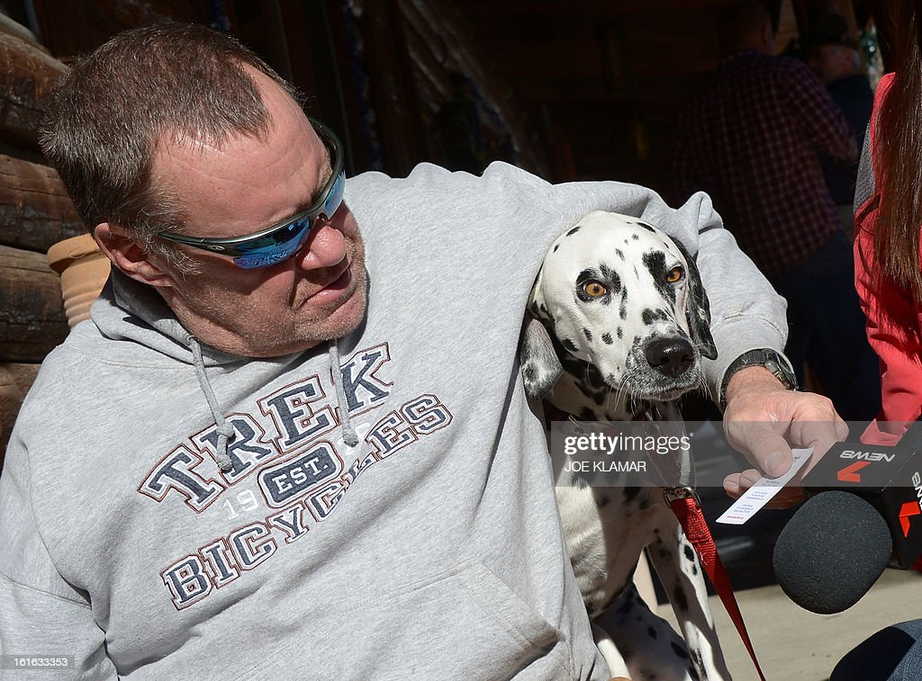Rick Heltebrake, who called police informing them that fugitive Christopher Dorner had hijacked his car, talks to the media with his dog Suni about the ordeal in Angelus Oaks, California, February 13, 2013. Suspected cop killer Dorner is believed to have been killed in a shoot-out at a cabin in the San Bernardino Mountains.