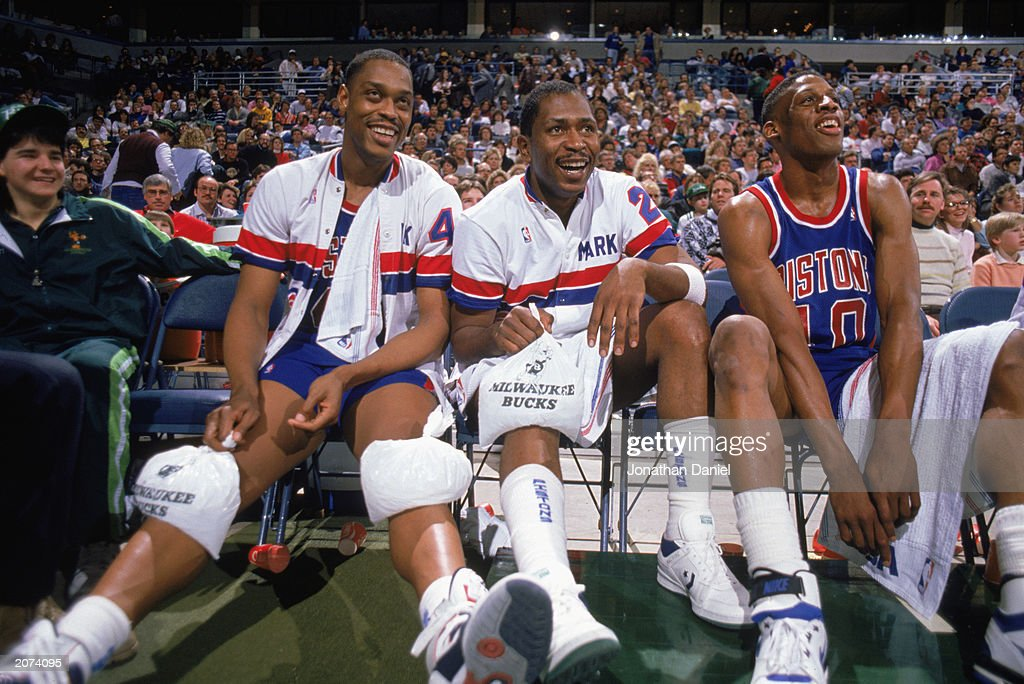 Rick Mahorn Mark Aguirre and Dennis Rodman of the Detroit Pistons watch the game as they rest on the bench during a game against the Milwaukee Bucks...