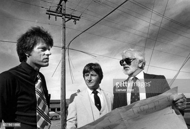 Rick Mardock left of United Cable Television and Perry Rogan center and Bill Brown of American Television and Communications study map at corner of...