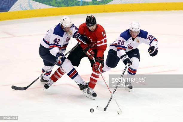 Rick Nash of Canada attempts to control the puch against David Backes and Ryan Suter of the United States during the ice hockey men's preliminary...