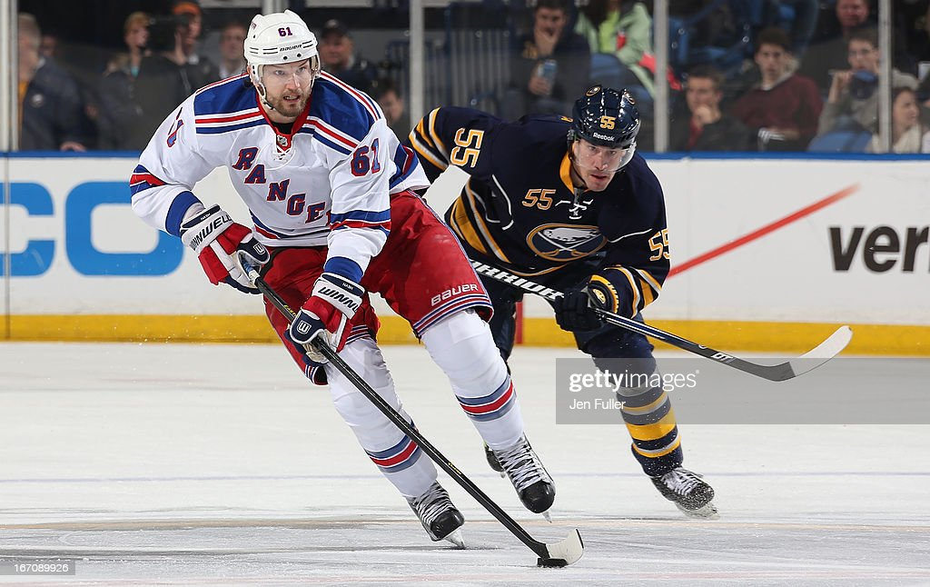 Rick Nash #61 of the New York Rangers carries the puck up ice as Jochen Hecht #55 of the Buffalo Sabres follows from behind at First Niagara Center on April 19, 2013 in Buffalo, New York.