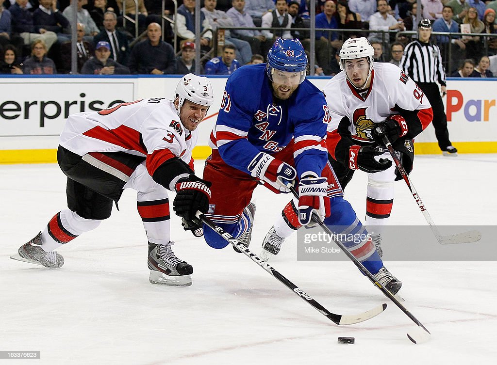 Rick Nash #61 of the New York Rangers controls the puck against Marc Methot #3 of the Ottawa Senators at Madison Square Garden on March 8, 2013 in New York City.