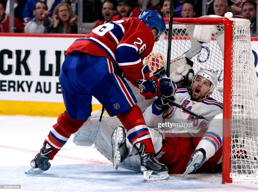 Rick Nash #61 of the New York Rangers crashes into Dustin Tokarski #35 of the Montreal Canadiens during Game Five of the Eastern Conference Final in the 2014 NHL Stanley Cup Playoffs at Bell Centre on May 27, 2014 in Montreal, Canada.