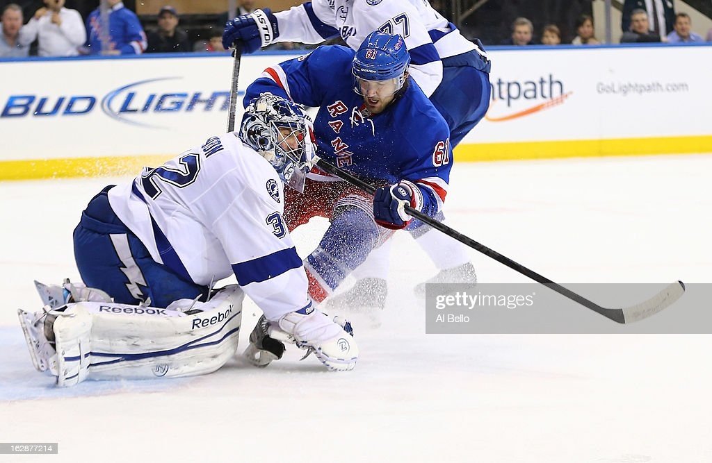 <a gi-track='captionPersonalityLinkClicked' href=/galleries/search?phrase=Rick+Nash&family=editorial&specificpeople=202196 ng-click='$event.stopPropagation()'>Rick Nash</a> #61 of the New York Rangers crashes into <a gi-track='captionPersonalityLinkClicked' href=/galleries/search?phrase=Mathieu+Garon&family=editorial&specificpeople=206119 ng-click='$event.stopPropagation()'>Mathieu Garon</a> #32 of the Tampa Bay Lightning during their game at Madison Square Garden on February 28, 2013 in New York City.