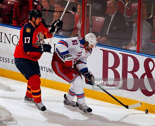 Rick Nash of the New York Rangers digs the puck out from the boards against Filip Kuba of the Florida Panthers at the BBT Center on April 23 2013 in...