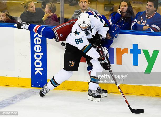 Rick Nash of the New York Rangers fights for the puck with Brent Burns of the San Jose Sharks in the first period at Madison Square Garden on October...