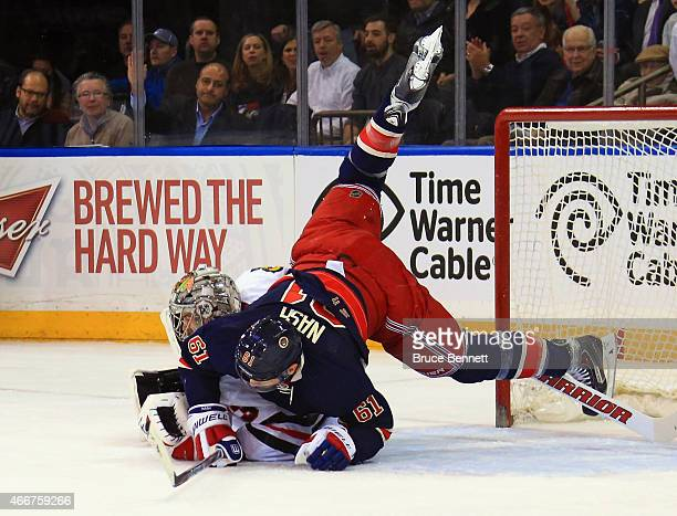 Rick Nash of the New York Rangers gets tripped up on Scott Darling of the Chicago Blackhawks during the first period at Madison Square Garden on...