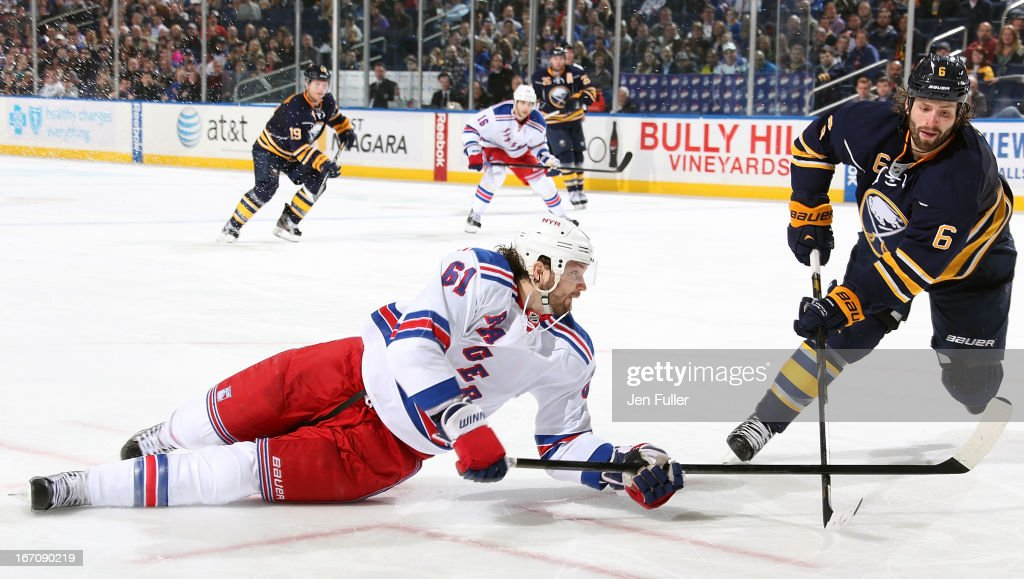 Rick Nash #61 of the New York Rangers looks for a loose puck alongside Mike Weber #6 of the Buffalo Sabres at First Niagara Center on April 19, 2013 in Buffalo, New York.