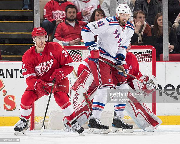 Rick Nash of the New York Rangers screens the view of goaltender Jared Coreau of the Detroit Red Wings while being defended by Nick Jensen of the...