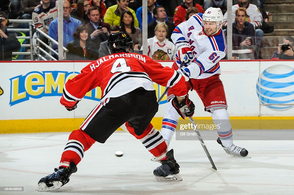<a gi-track='captionPersonalityLinkClicked' href=/galleries/search?phrase=Rick+Nash&family=editorial&specificpeople=202196 ng-click='$event.stopPropagation()'>Rick Nash</a> #61 of the New York Rangers shoots the puck against <a gi-track='captionPersonalityLinkClicked' href=/galleries/search?phrase=Niklas+Hjalmarsson&family=editorial&specificpeople=2006442 ng-click='$event.stopPropagation()'>Niklas Hjalmarsson</a> #4 of the Chicago Blackhawks during the NHL game on January 08, 2014 at the United Center in Chicago, Illinois.