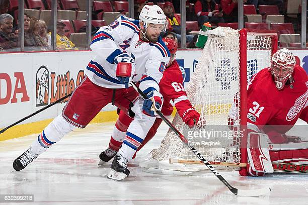 Rick Nash of the New York Rangers skates around the net with the puck in front of goaltender Jared Coreau of the Detroit Red Wings followed by Xavier...