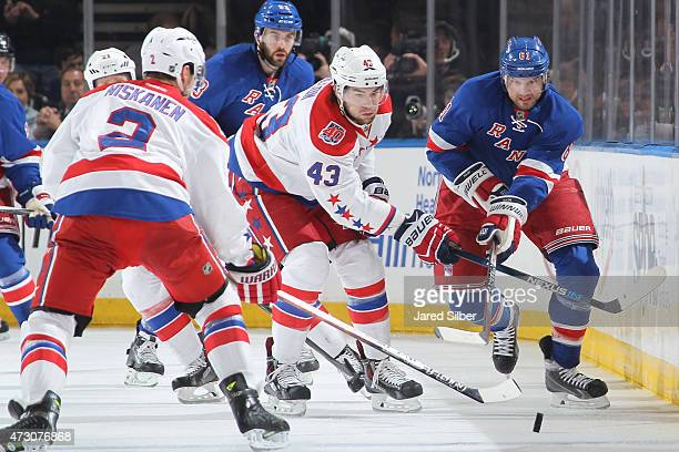 Rick Nash of the New York Rangers skates the puck up the ice against Tom Wilson and Matt Niskanen of the Washington Capitals in Game Five of the...