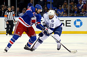 Rick Nash of the New York Rangers skates with the puck in the first period as Brenden Morrow of the Tampa Bay Lightning defends in Game One of the...