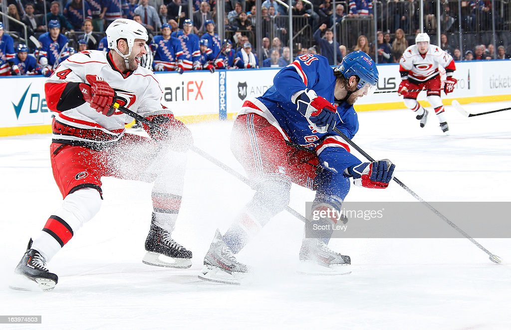 <a gi-track='captionPersonalityLinkClicked' href=/galleries/search?phrase=Rick+Nash&family=editorial&specificpeople=202196 ng-click='$event.stopPropagation()'>Rick Nash</a> #61 of the New York Rangers spins past <a gi-track='captionPersonalityLinkClicked' href=/galleries/search?phrase=Jay+Harrison&family=editorial&specificpeople=714374 ng-click='$event.stopPropagation()'>Jay Harrison</a> #44 of the Carolina Hurricanes at Madison Square Garden on March 18, 2013 in New York City.