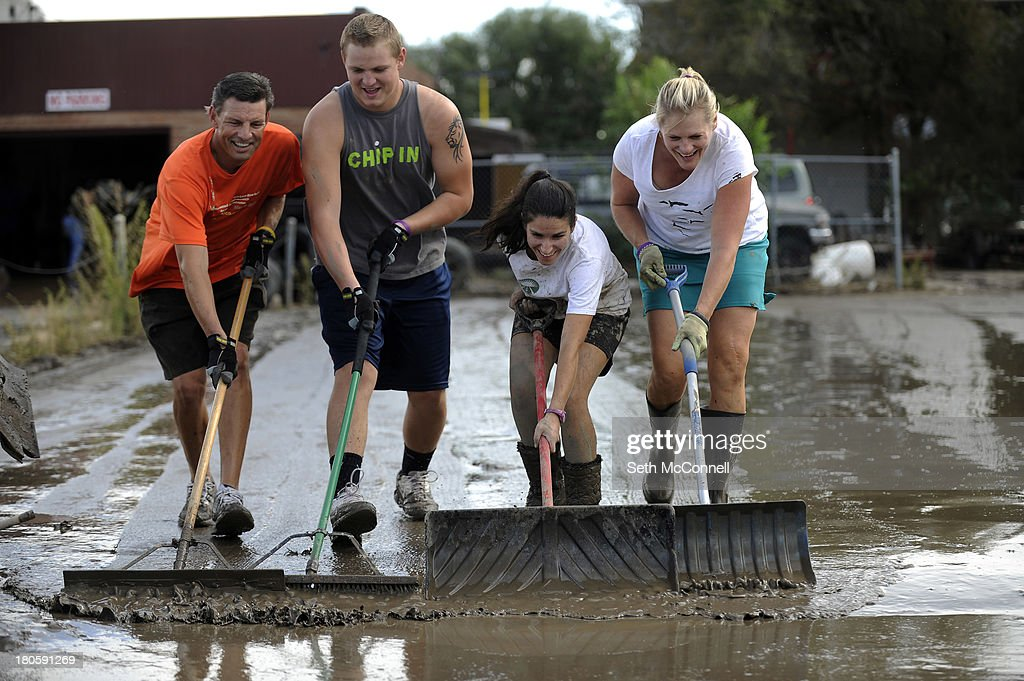 Rick Phillips, left, Logan Phillips, 18, Sharon Shaw and Suzanne Phillips create a human plow as they push mud and flood waters out of the parking lot of a joint business on Boston Ave in Longmont, Colorado on September 14, 2013. Clean up began on Saturday in downtown Longmont following heavy flooding in previous days.