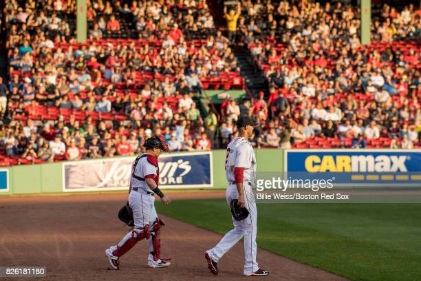 Rick Porcello and Christian Vazquez of the Boston Red Sox walk toward the dugout before a game against the Chicago White Sox on August 3 2017 at...
