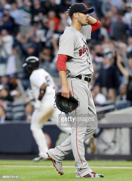Rick Porcello of the Boston Red Sox reacs as Chris Carter of the New York Yankees rounds first base after Carter hit a three run home run in the...