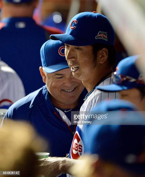 Rick Renteria of the Chicago Cubs laughs with relief pitcher Kyuji Fujikawa after the eighth inning against the Pittsburgh Pirates at Wrigley Field...
