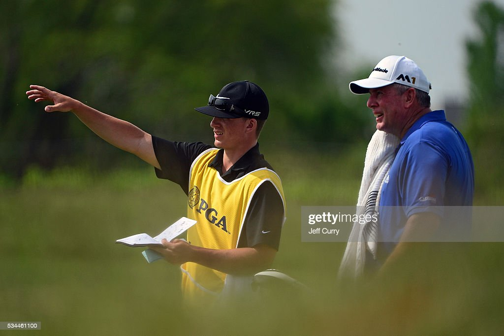 Rick Schuller discusses his fairway shot on the ninth hole with his caddy during the first round 2016 Senior PGA Championship presented by KitchenAid at the Golf Club at Harbor Shores on May 26, 2016 in Benton Harbor, Michigan.