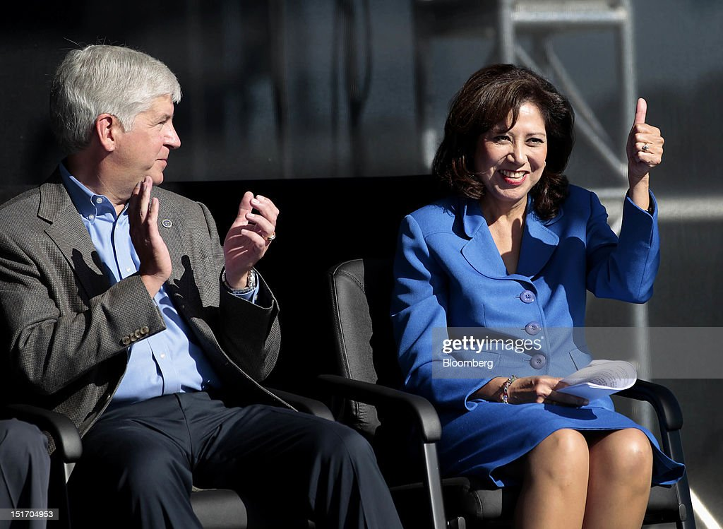 Rick Snyder governor of Michigan left applauds while Hilda Solis US secretary of labor gestures outside of the Ford Motor Co assembly plant in Flat...