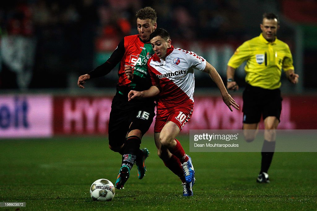Rick ten Voorde of NEC pushes Tommy Oar of Utrecht off the ball as referee, Bjorn Kuipers watches the action during the Eredivisie match between NEC Nijmegen and FC Utrecht at the McDOS Goffertstadion on November 24, 2012 in Nijmegen, Netherlands.
