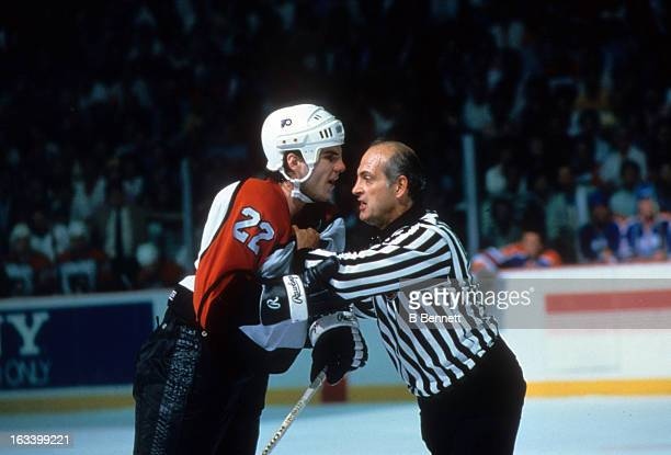 Rick Tocchet of the Philadelphia Flyers is restrained by linesman John D'Amico during the 1987 Stanley Cup Finals against the Edmonton Oilers in May...