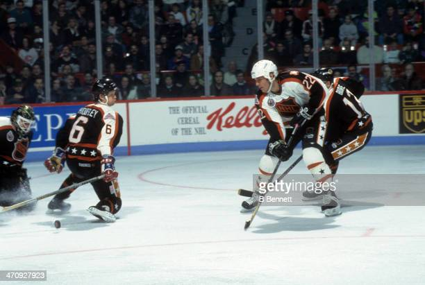 Rick Tocchet of the Wales Conference and the Pittsburgh Penguins shoots as Phil Housley of the Campbell Conference and the Winnipeg Jets tries to...