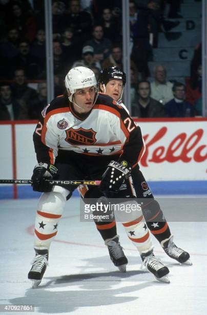 Rick Tocchet of the Wales Conference and the Pittsburgh Penguins skates on ice as he is defended by Phil Housley of the Campbell Conference and the...
