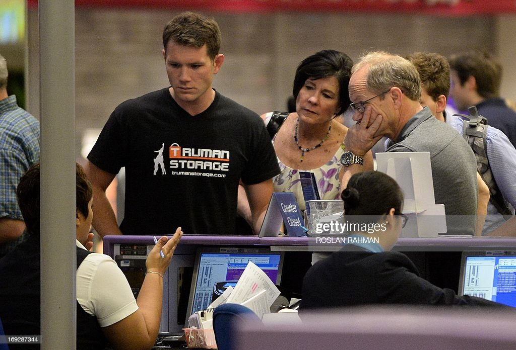 Rick Todd (R) and his wife Mary (2nd L) with their two sons, John (L) and Dylan (behind partly seen) wait at the departure hall check-in counter of Changi International Airport in Singapore on May 23, 2013. Two US pathologists on May 22 supported Singapore police findings that American scientist Shane Todd found hanged last year in the city-state committed suicide and was not murdered as his family claims. .